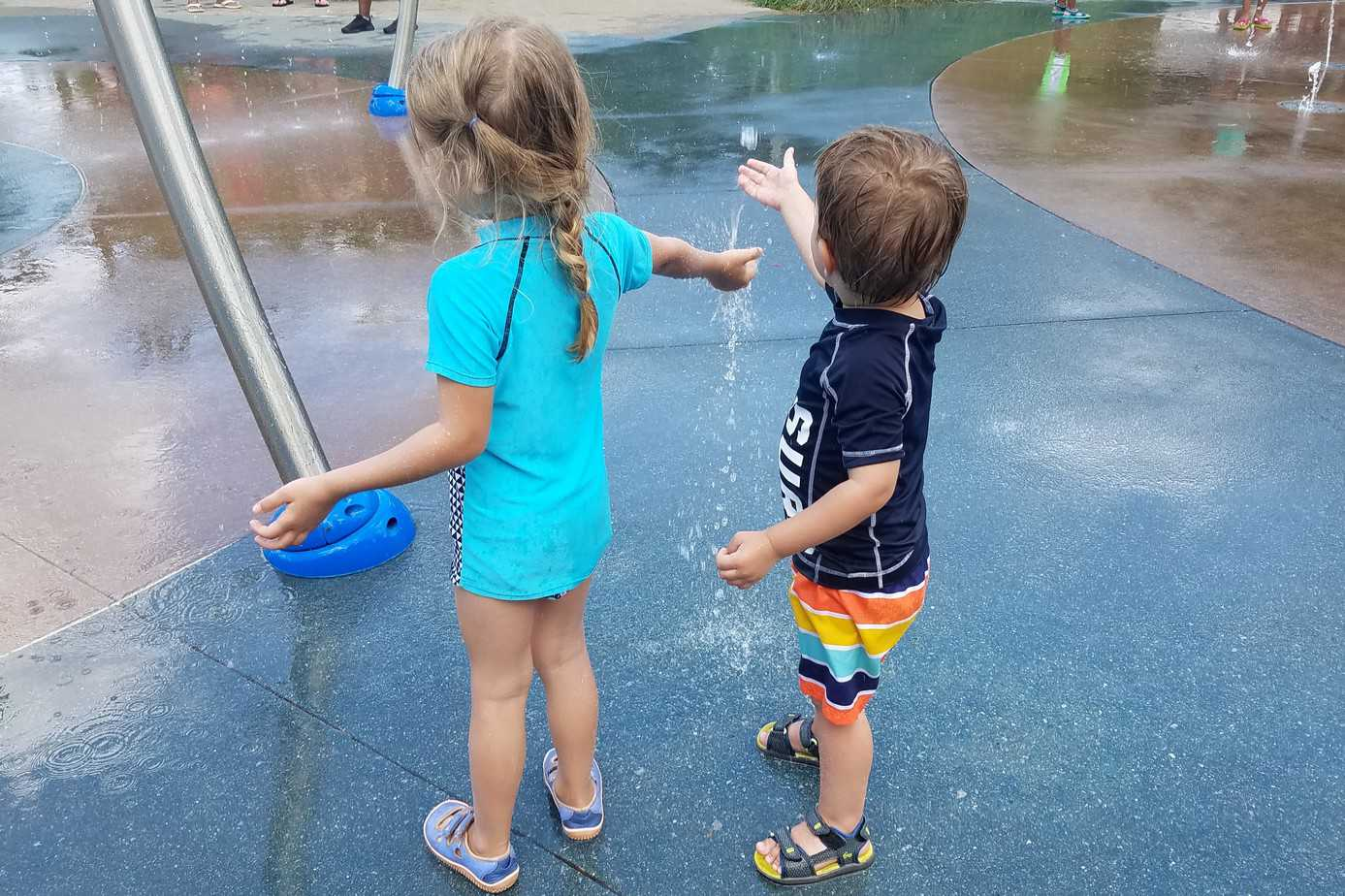 Preschool girl and boy playing in a splash pad on a hot summer day.