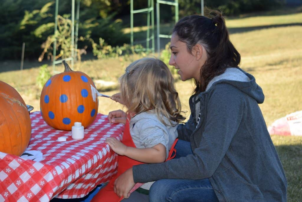 A girl painting a pumpkin with her mom.