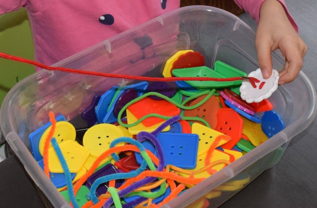 A  girl playing with a button sensory bin.