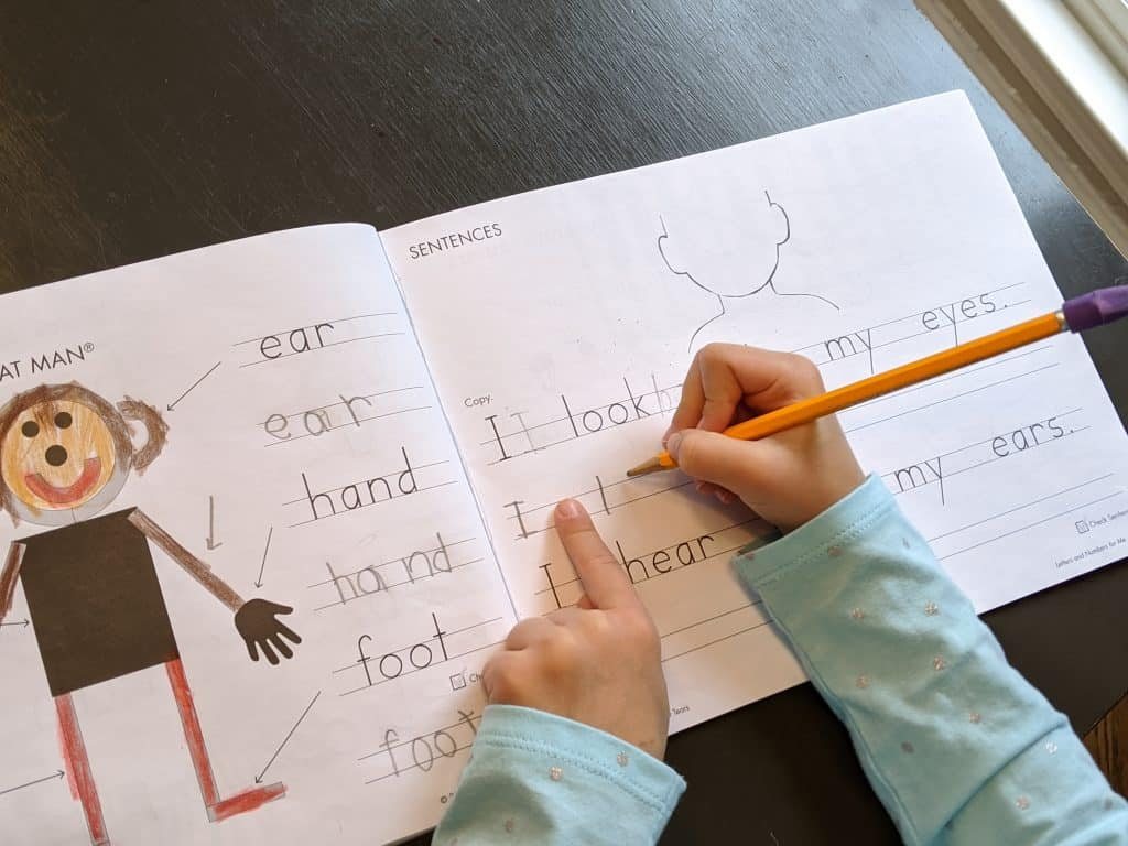 A girl practicing handwriting in a workbook.