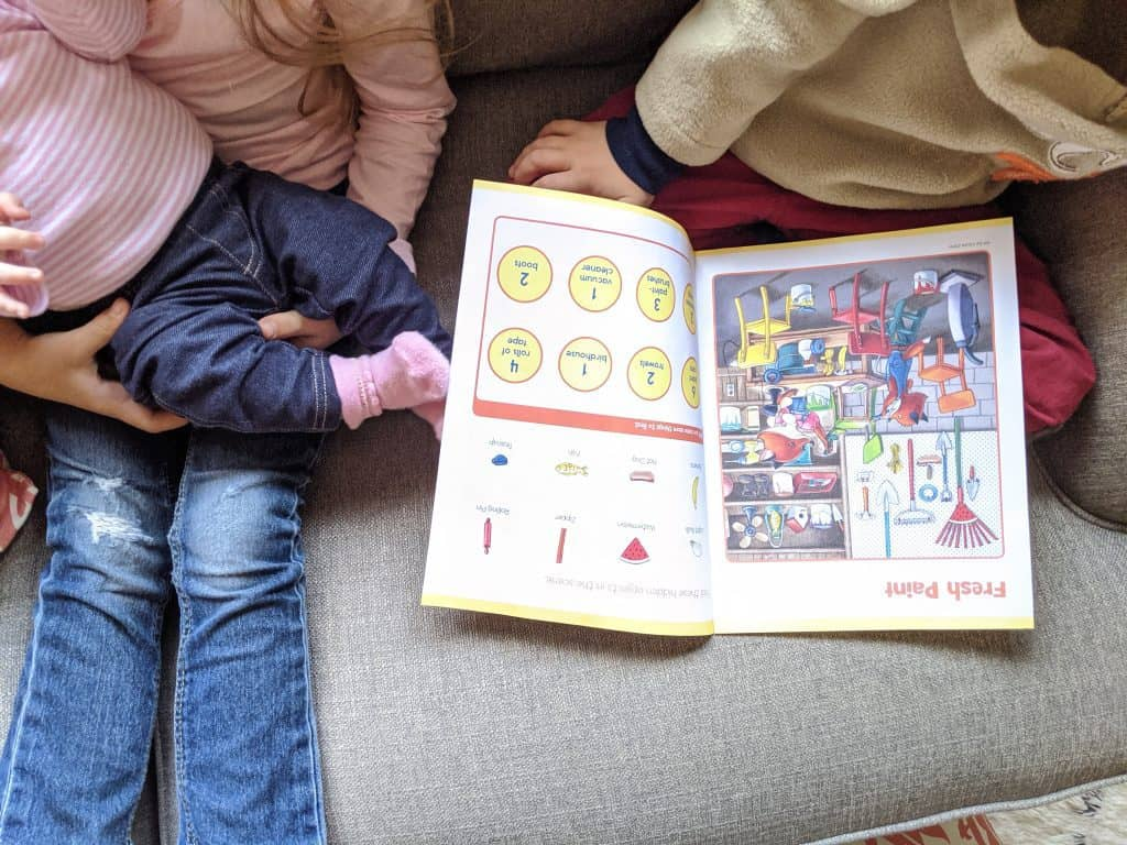 A boy and a girl holding a baby with a magazine between them.