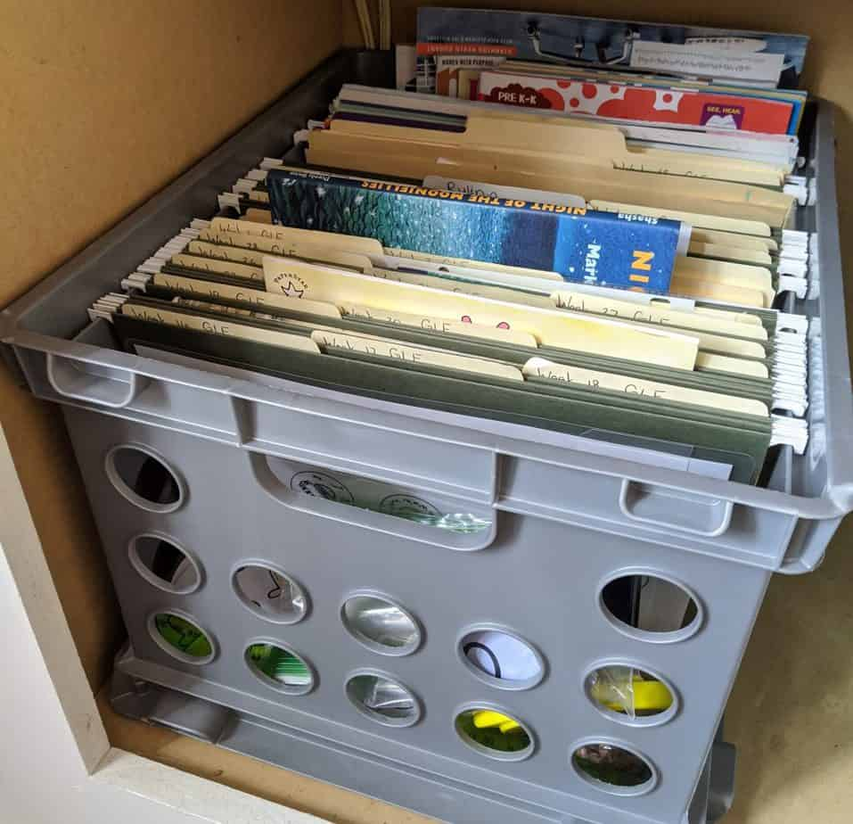 A crate with file folders with homeschooling supplies