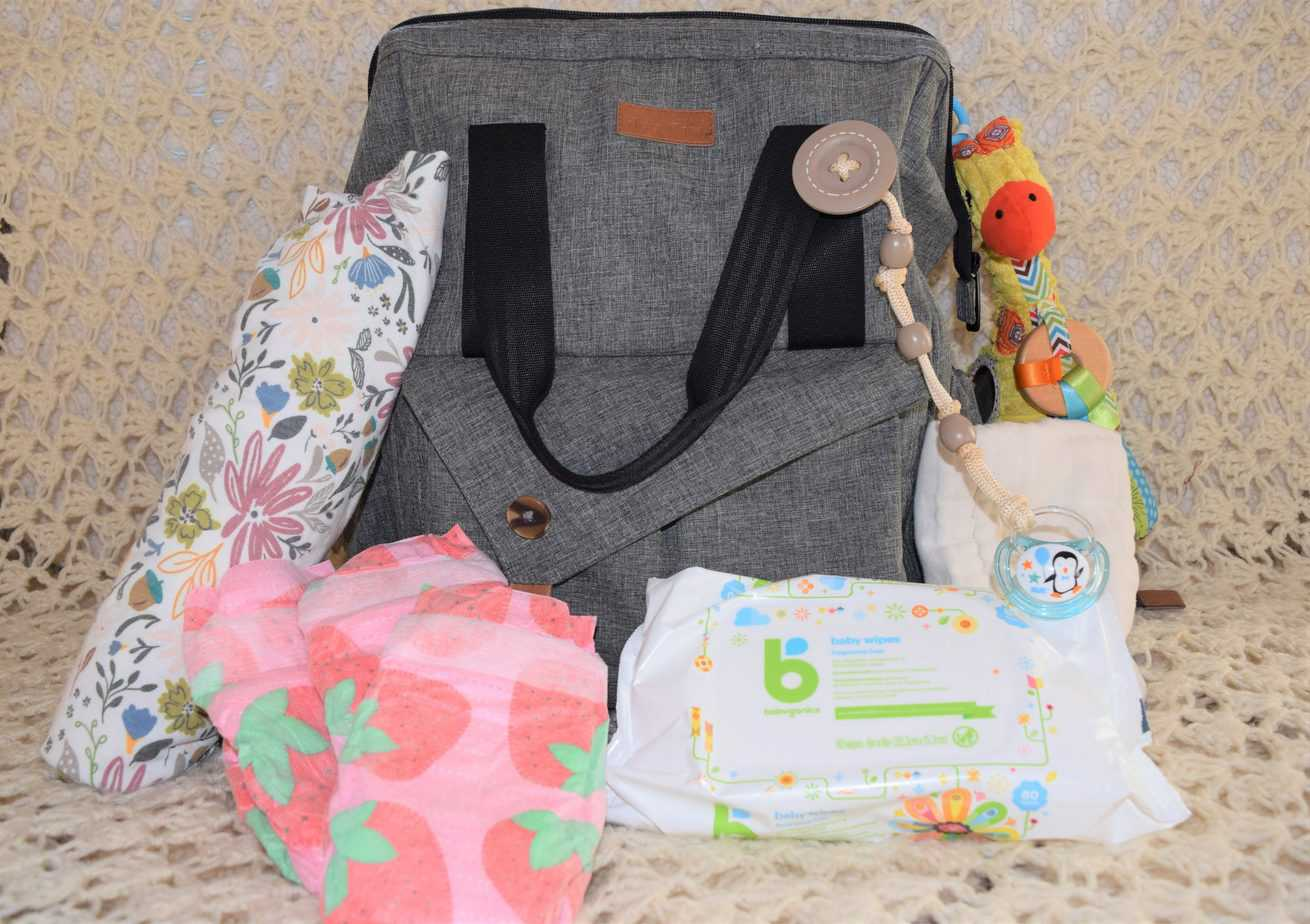 Diaper bag and diaper bag essentials grouped together