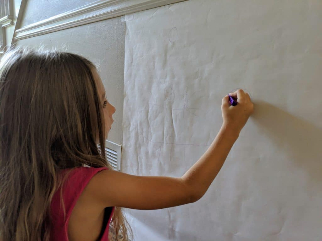 A girl drawing on easel paper.