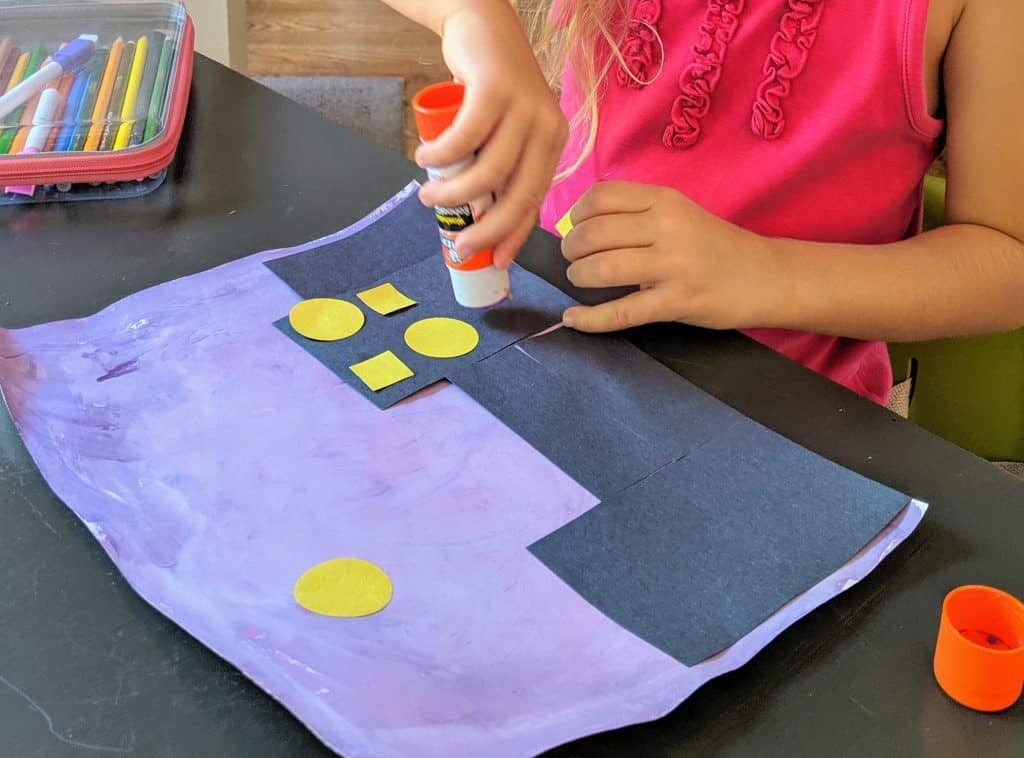 A girl gluing shapes onto her cityscape craft.