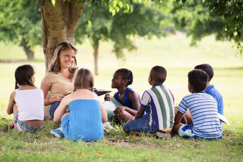 A group of homeschool kids sitting outside during scholastic book club